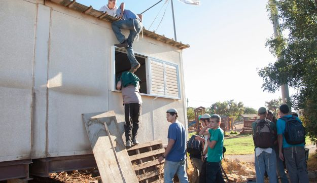 Settler youths climb onto a structure in Migron.