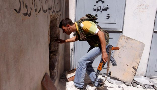 A member of the Free Syrian Army walks trough a hole during clashes with Syrian government forces.