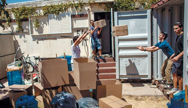 Migron residents loading boxes onto trucks on August 4, 2012