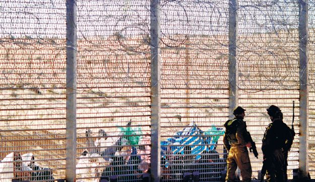African migrants looking through the fence at the Egyptian-Israeli border on August 4, 2012.