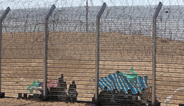 Eritreans caught between Israel and Egypt's border fences, on Wednesday.