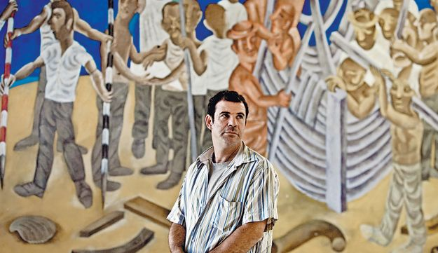 Ofek in front of one of his father's murals at Moshav Kfar Uria.