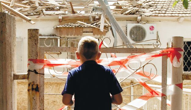 A child looking at the remains of a house hit by a rocket in Netivot