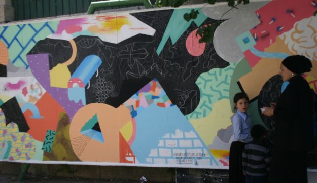 Residents of Musrara stop to look at an installation done by a visiting German street art group.