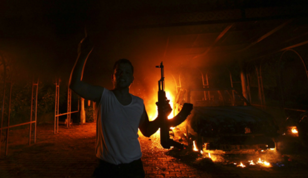 A protester reacts as the U.S. Consulate in Benghazi is seen in flames during a protest by an armed