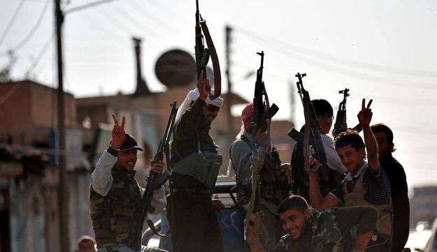 Syrian rebels make victory signs near the border with Turkey last year.