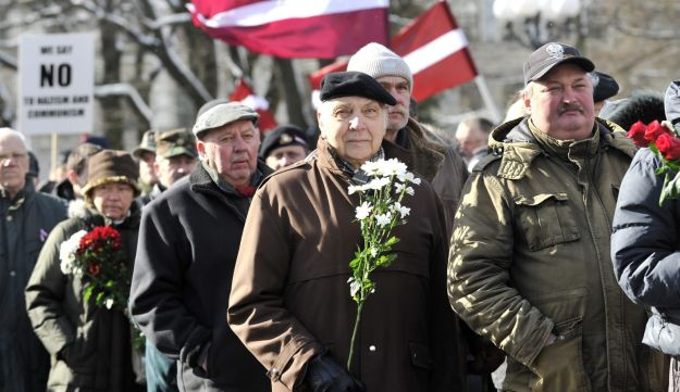 People carry Latvian flags as they march to the Freedom Monument to commemorate World War II veteran
