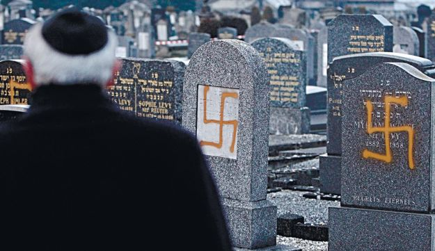 Francis Levy inspecting tombstones desecrated by vandals with Nazi swastikas.
