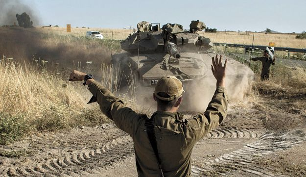 An IDF soldier directing a tank near the Quneitra crossing with Syria, June 5, 2013.