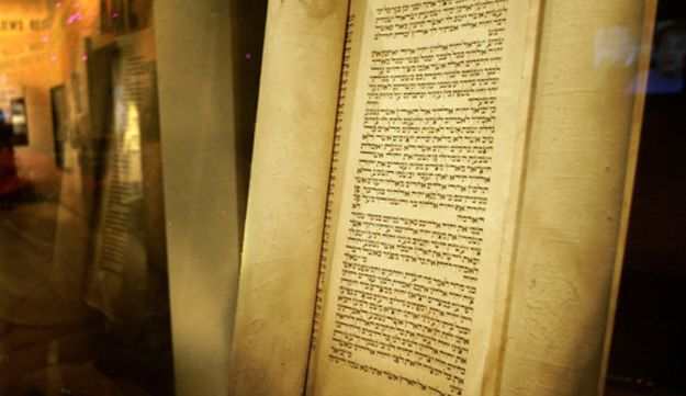 A Torah parchment scroll on display in a museum.