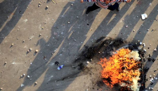 An anti-Muslim Brotherhood demonstrator throws stones during clashes in Cairo's Tahrir Square.
