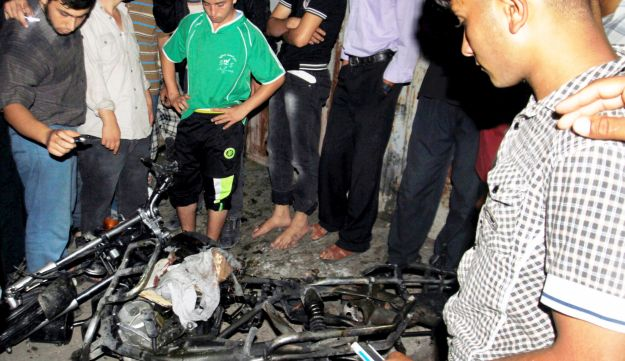 Palestinians gather around the wreckage of a motorcycle following an Israeli airstrike in Jabalia.