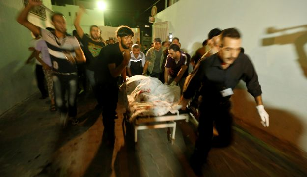 Palestinians wheel the body of a militant at a hospital - Reuters - October 13, 2012.