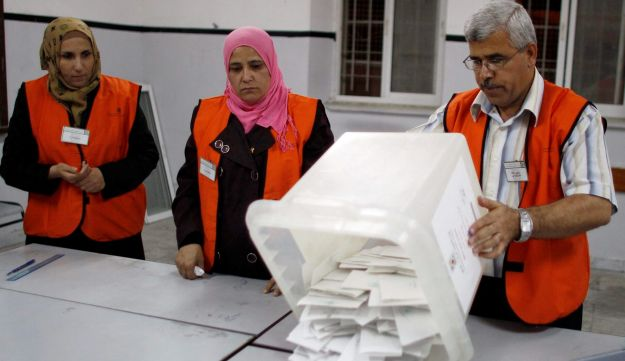 Election officials prepare to count ballots after the polls closed