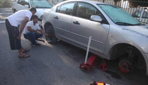 An Abu Ghosh resident replaces his tires after they were slashed.