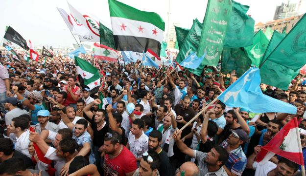 Lebanese protestes wave Syrian revolutionary flags, national flags and Islamic flags