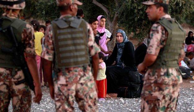 Jordanian soldiers watch over Syrian refugees fleeing violence in their country.