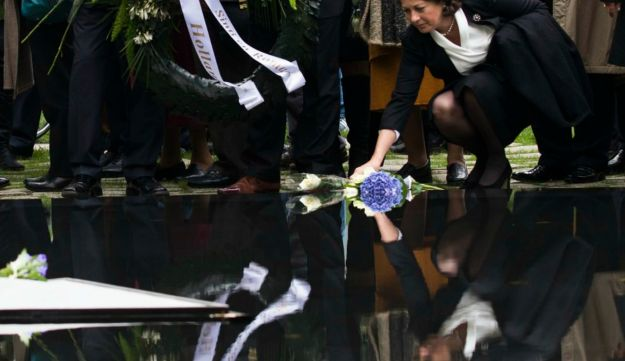 A woman lays down a flower during the inaugural ceremony of the memorial to the murdered European Si