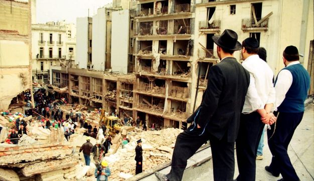 Jewish men look on as rescuers at bombing site - Bloomberg - July 18, 1994.