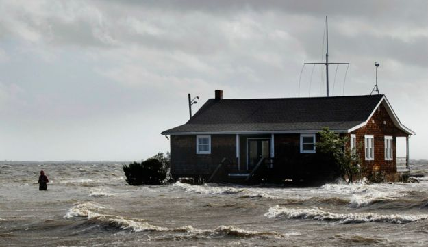 A man walking away from a building that has been surrounded by water pushed up by Hurricane Sandy