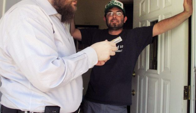 Rabbi Chaim Bruk, left, prepares a mezuzah to install on the doorway of Jake Matilsky's home