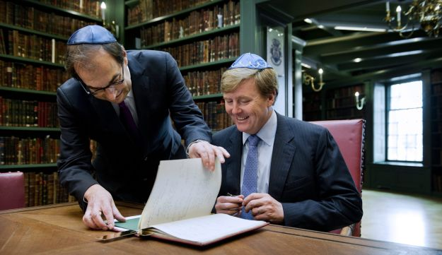 Willem-Alexander of the Netherlands, right, signs the guestbook in the presence of Joel Cahen