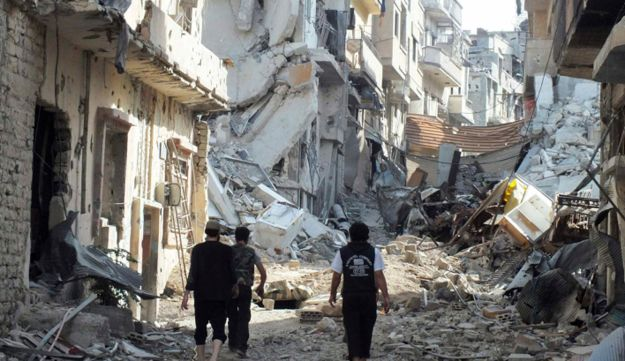 Free Syrian Army fighters walk on rubble of damaged buildings, Juret al-Shayah, Homs, Nov. 1, 2012.