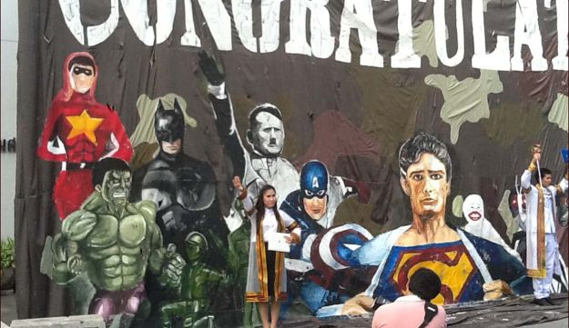 A Thai student poses for a picture in front of the offensive mural.