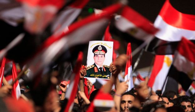 Anti-Morsi protesters hold a poster of the head of Egypt's armed forces General Abdel Fattah al-Sisi
