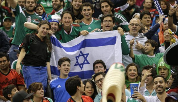 Fans hold up an Israel flag on the tribune during an international friendly soccer match
