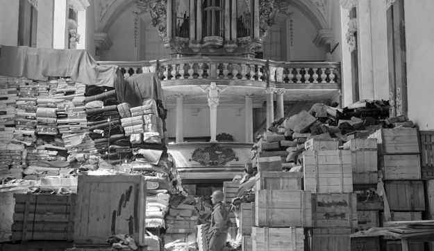 an American soldier stands among German loot stored in a church at Elligen, Germany