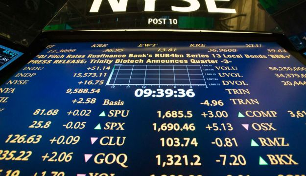 The New York Stock Exchange logo stands above a board displaying stock prices.