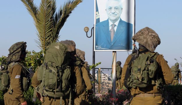 Israeli soldiers stand next to a poster of Palestinian president Abbas.