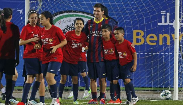 FC Barcelona's Lionel Messi poses for a photo with young Palestinian players during a soccer clinic