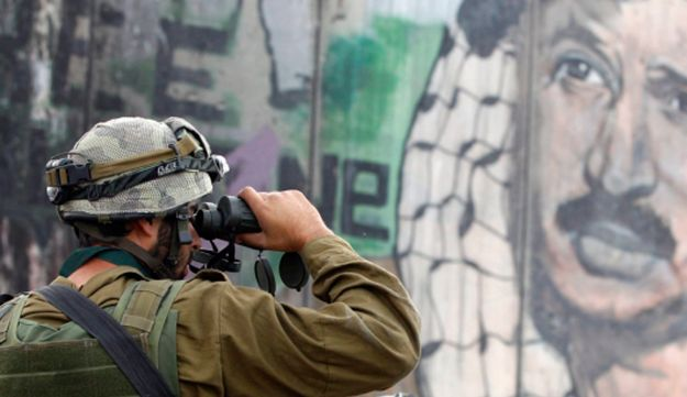 An IDF soldier in front of a mural depicting the late Palestinian leader Yasser Arafat