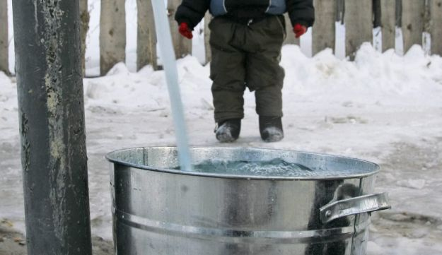 A boy watches his father gets water from a hydrant in Khabarovsk, on the banks of the Amur river, Ru