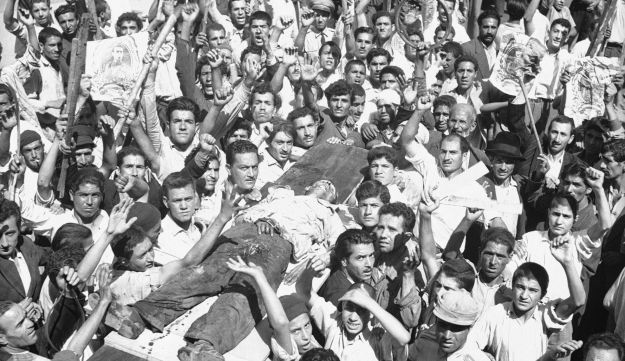 File photo: The body of a man killed in a pro-Shah riot which swept through Tehran is carried aloft by demonstrators. Aug. 19, 1953.