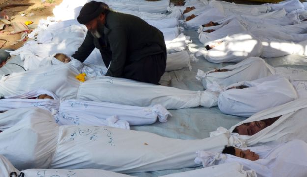 A man holds the body of a dead child in Syria - Reuters