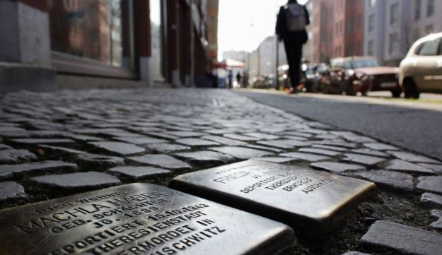 People pass so called 'Stolpersteine', or stumbling stones which remember to Jews killed by the Nazis, Berlin, Germany, March 10, 2014