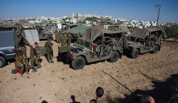 Israeli soldiers stand next to an Army post at the outskirts of Hebron June 14, 2014.