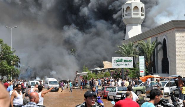 Smoke is seen above people gathering outside a mosque on the site of a powerful explosion in Tripoli