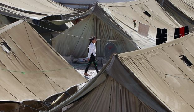 A Syrian refugee girl walks at a temporary refugee camp in the eastern Lebanese town of Marj near th