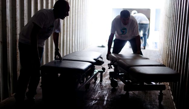 Volunteers load hospital beds into a container destined for Syria.