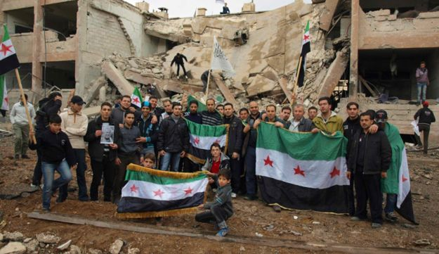 Demonstrators pose with Syrian opposition flags at the site of buildings badly damaged after a Syria