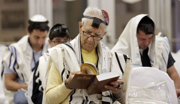Jacob Aday, of Venezuela, center, prays during a weekly service at the Sky Lake Synagogue, Wednesday