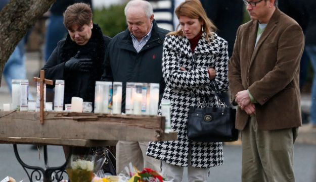 People pay respects at a makeshift memorial outside of St. Rose of Lima Roman Catholic Church.