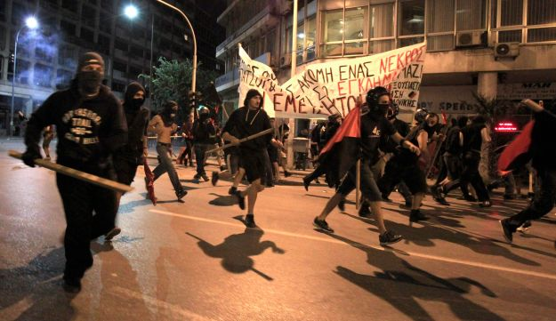Protesters run in the street as they clash with police in Thessaloniki, Greece.