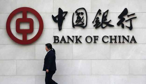 A woman walks past a Bank of China sign in Bejing,