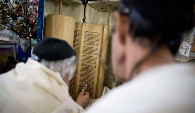 Iranian Jewish men read from the Torah scroll during morning prayers at Youssef Abad synagogue
