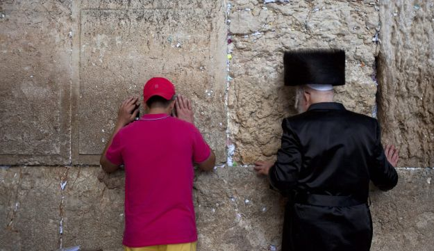 An ultra-Orthodox man prays alongside a tourist at the Western Wall. Wednesday, September 4, 2013.